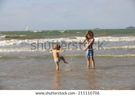 Two little girls having fun on the beach. - stock photo