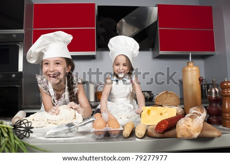 two little girls having fun on the kitchen table with raw food, clothing cooks - stock photo