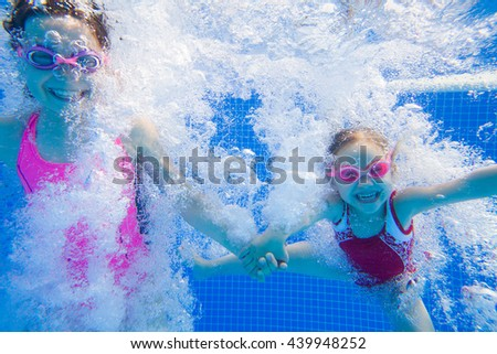 two little girls having fun with bubbles in the pool - stock photo