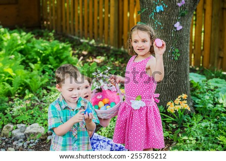 Two little girls hold a basket with color dyed Easter eggs outdoors in a beautiful garden setting in the spring season.  A little boy walks by looking at his blue egg.  Part of a series.  - stock photo