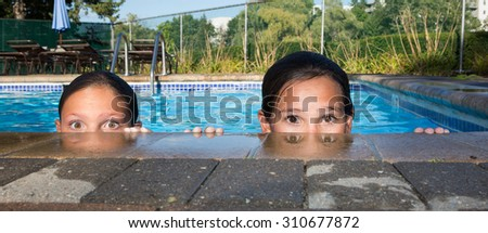 Two little girls in a pool peeking over the edge looking right at the camera with big eyes