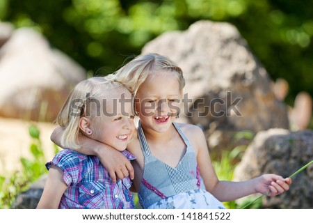 Two little girls in the park sitting arm in arm laughing happily as they enjoy the freedom and the summer sunshine