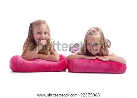 two little girls lying an pink cushions having fun. isolated on white background - stock photo