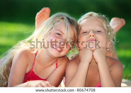 two little girls lying down in the grass and having fun - stock photo