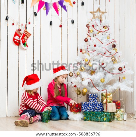 two little girls open christmas presents sitting on the floor near decorated new year tree