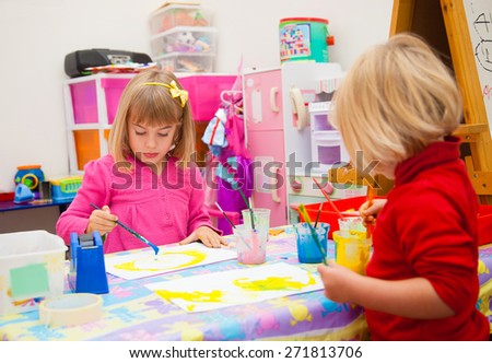 Two little girls painting in their toy room - stock photo