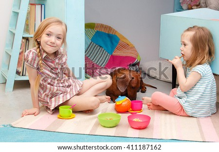 Two little girls play in the nursery