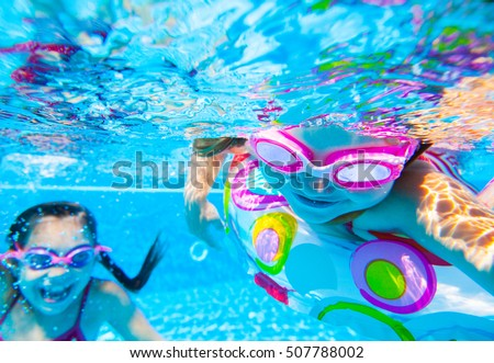 two little girls played under water in the pool
