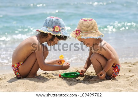 Two little girls playing on the beach - stock photo
