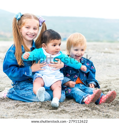 two little  girls  playing with a baby boy  on the beach on a sunny summer day - stock photo