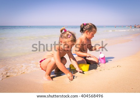 Two little girls playing with sand on the seashore. - stock photo
