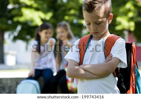 Two little girls pointing to the little sad boy, focus on foreground - stock photo