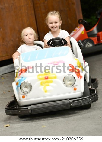 Two little girls riding toy car on streets of city.  - stock photo