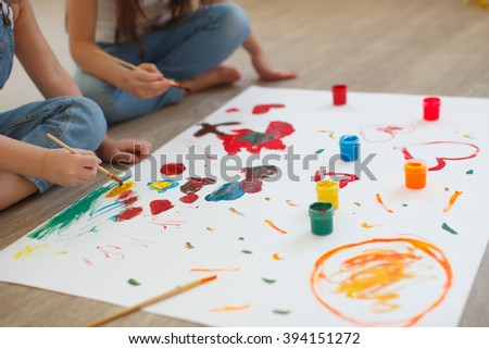 Two little girls, sisters draw painted in colorful paint hands - stock photo
