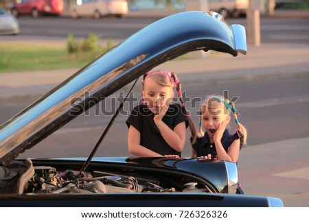 Two little girls sisters look surprised under the hood of the car.
