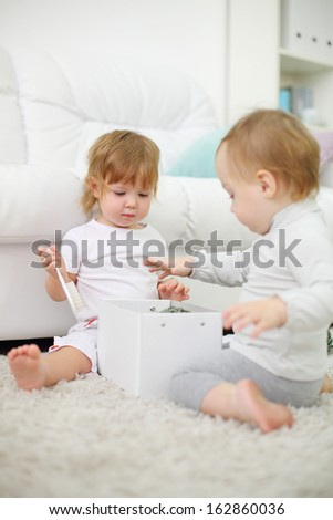 Two little girls sit on carpet and play with white box. Focus on left kid. Shallow depth of field.