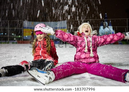 Two little girls sit on skating rink ice in evening under falling snow - stock photo