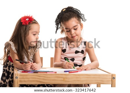 Two little girls sitting at table and dawing isolated on white background