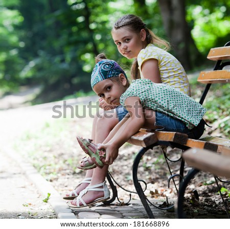 Two little girls sitting on a park bench in summer - stock photo