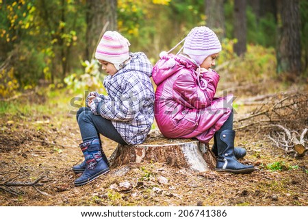 Two little girls sitting on tree stump in autumn forest. - stock photo