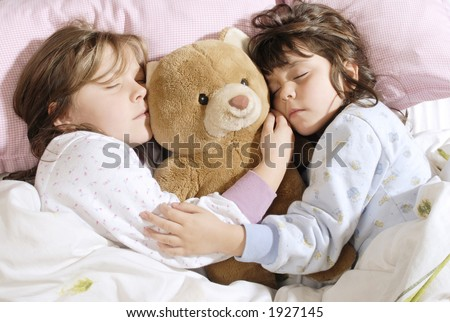 two little girls sleeping with a plush bear - stock photo