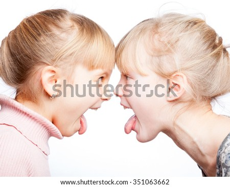 Two little girls stick out tongues teasing each other face to face - stock photo