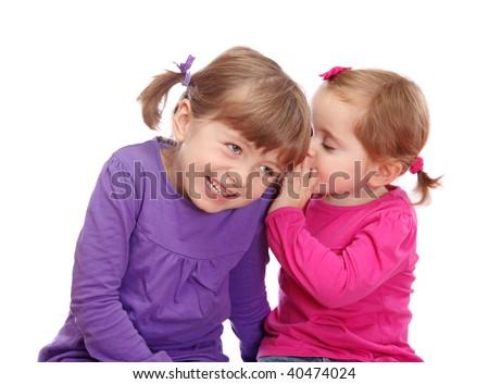 Two little girls telling secrets isolated on white background - stock photo