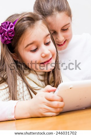 Two little girls using a touch pad together - stock photo