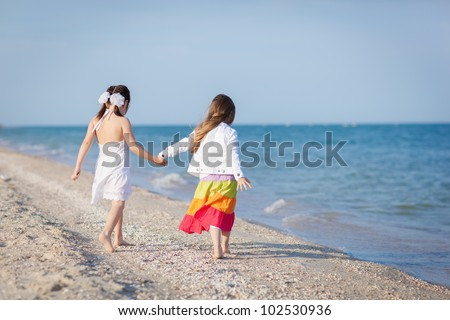 Two little girls walking at the beach - stock photo