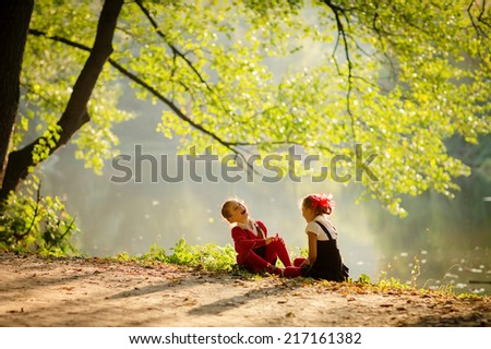 Two little girls walking in park after school - stock photo