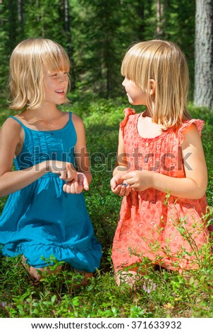 Two little girls wearing blue and red summer dress picking and eating blueberries in a forest - stock photo