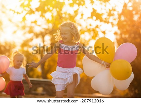 Two little girls with balloons in the park - stock photo