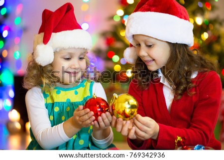 two little girls with presents around the Christmas tree