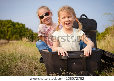 two little girls with suitcase on the road - stock photo