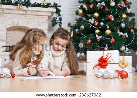 Two little girls writes letter to Santa - stock photo