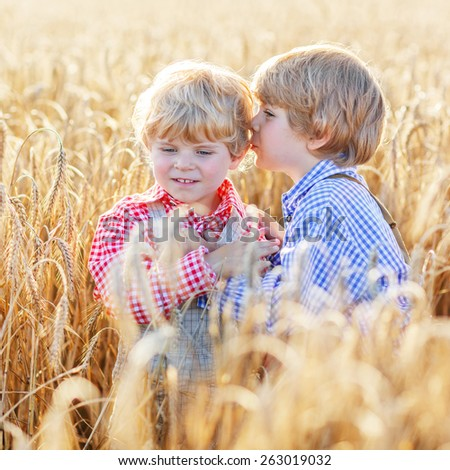 Two little happy friends having fun and speaking on yellow wheat field in summer. Active outdoors leisure with children on warm summer day. Children playing together. - stock photo