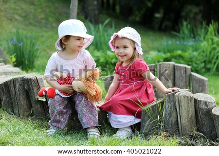 Two little happy smiling girl friends in summer dresses and with doll have a fun on the stub in the meadow, playing outdoors in spring park, summer and spring outdoors - stock photo