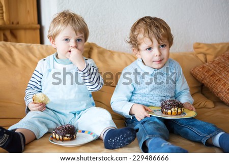 Two little kid boys eating sweet cakes together. Family of two brothers. - stock photo