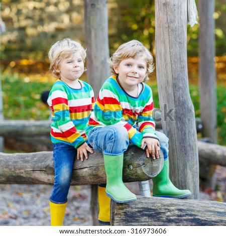 Two little kid boys in colorful shirts with stripes and gumboots having fun with playing on playground on warm, autumn day, outdoors - stock photo