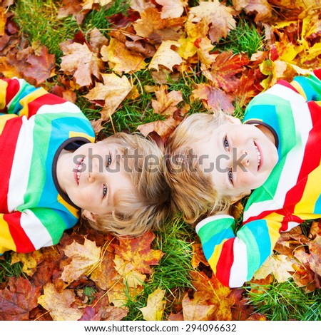 Two little kid boys lying in autumn leaves in colorful clothing. Happy siblings having fun in autumn park on warm day. - stock photo