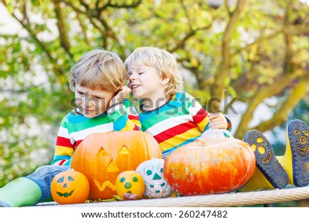 Two little kid boys making jack-o-lantern for halloween in autumn garden, outdoors. Happy children having fun together with traditional party - stock photo