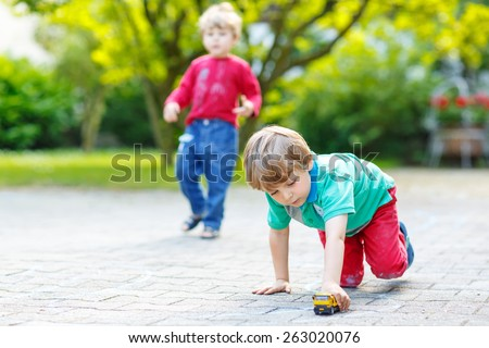 Two little kid boys playing together with car toys in summer garden. Active outdoors leisure for children on hot summer sunny day. Family lifestyle - stock photo