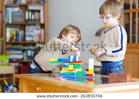 Two little kid boys playing with lots of colorful plastic blocks indoor. Children having fun with building and creating. - stock photo