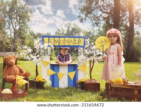 Two little kids are selling lemonade at a homemade lemonade stand on a sunny day with a price sign for an entrepreneur concept. - stock photo
