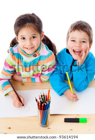 Two little kids at the table draw with crayons, isolated on white - stock photo