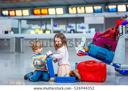 Two little kids, boy and girl with suitcases at the airport, indoors and waiting for vacations. Happy children, twins, brother and sister exciting about air travel trip and flying with airplane.