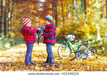 Two little kids boys, best friends in autumn forest. Older brother helping younger child to put his bike helmet. Active siblings with bicycles. - stock photo