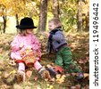 Two little kids dating with hand lifts onto shoulder in autumn park - stock photo