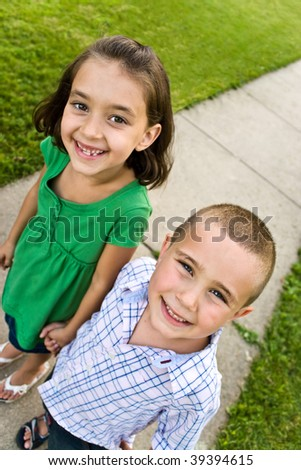 Two little kids holding hands as they walk down the sidewalk.  Plenty of copy space for your text. - stock photo