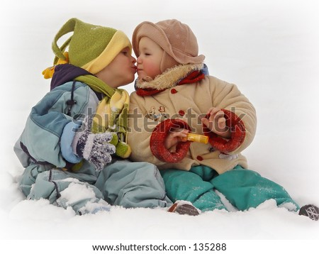 two little kids kissing in the snow - stock photo